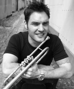 black and white photo of paul williamson holding his trumpet