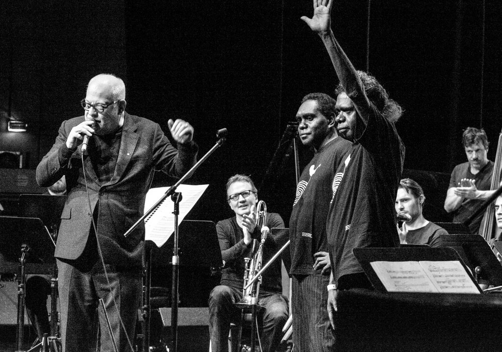 Paul Grabowsky on stage with members of the Young Wagilak Group and the Australian Art Orchestra
