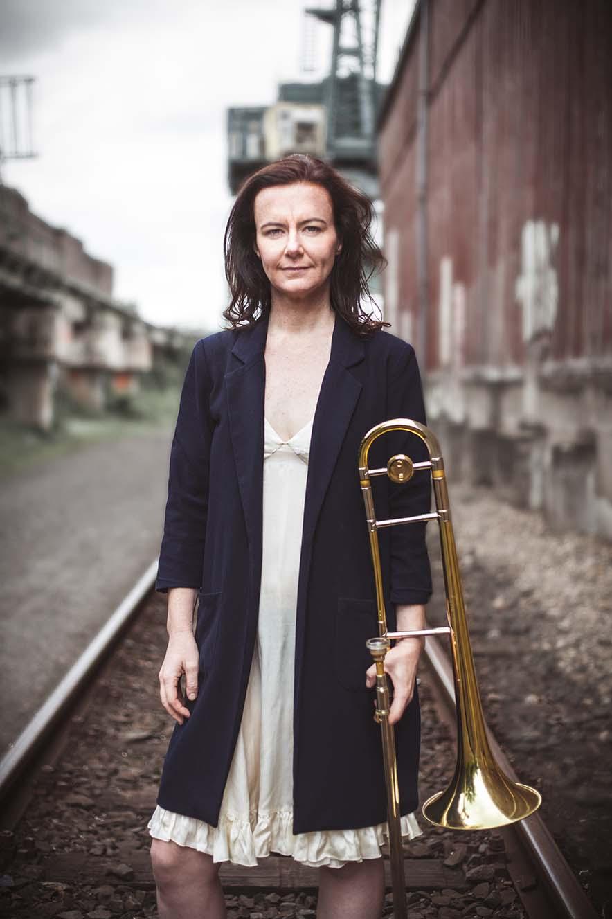 trombone player on railway tracks